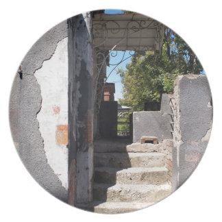 砕けるプラスターが付いている古い建物のポーチ お皿