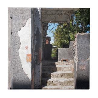 砕けるプラスターが付いている古い建物のポーチ 正方形タイル小