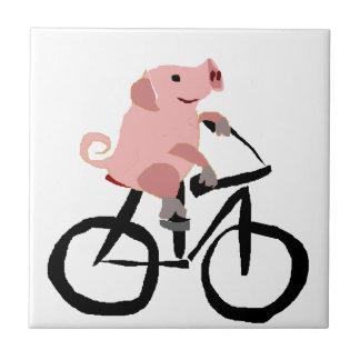 おもしろいなピンクのブタの乗馬の自転車 タイル