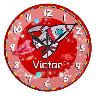 おもしろいの子供の男の子は宇宙の赤い柱時計をロケットで行かせます クロック