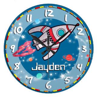 おもしろいの子供の男の子は宇宙の青い水の柱時計をロケットで行かせます ラージ壁時計