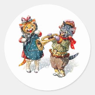 かわいい猫は雪のトランペット及び三角形を遊びます ラウンドシール