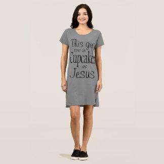 この女の子はカップケーキおよびイエス・キリストで走ります ドレス