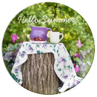 こんにちは庭の夏の茶そしてプラム 磁器プレート