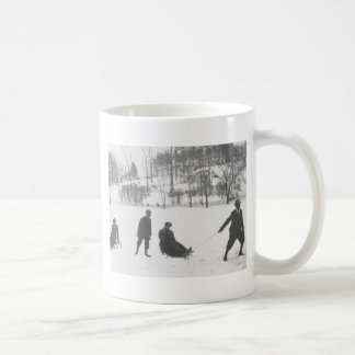 そりの2人の女の子を引っ張っている2人の男の子 コーヒーマグカップ