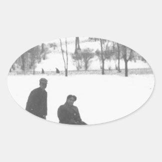 そりの2人の女の子を引っ張っている2人の男の子 楕円形シール