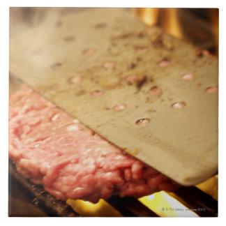 へらが付いているハンバーガーハンバーグを平らにします タイル