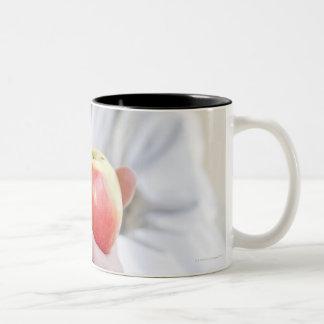りんごを握っている医者のポートレート ツートーンマグカップ