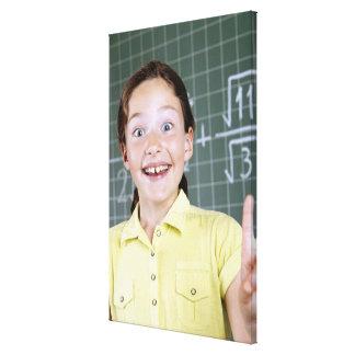 アイディアを持っている黒板の前の若い女の子 キャンバスプリント