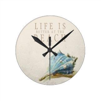 アイボリーの貝殻の生命はビーチの時計でよりよいです ラウンド壁時計