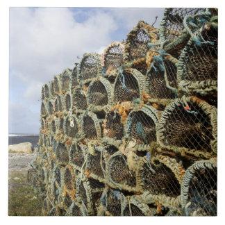 アイルランドの海岸線のロブスターのカニを捕る枝編みかごの山 タイル