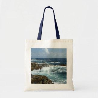 アルバの岩が多い海岸および青い海 トートバッグ
