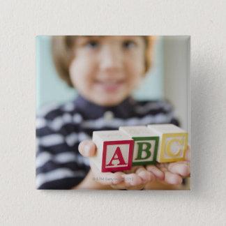 アルファベットのブロックを握っているヒスパニックの男の子 5.1CM 正方形バッジ