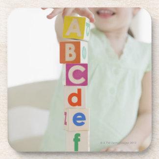 アルファベットのブロックを積み重ねている混血の女の子 コースター