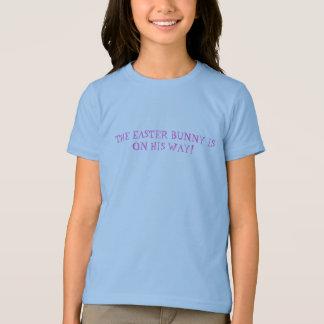 イースターのウサギは彼の方法女の子のワイシャツにあります Tシャツ