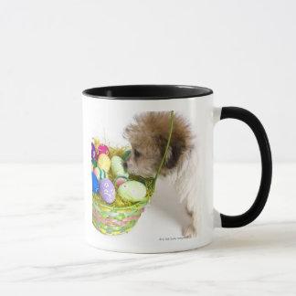 イースターバスケットでくんくんかいでいる混合された品種子犬 マグカップ