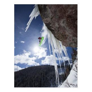 オスのスノーボーダーは氷の滝を離れて跳びます ポストカード