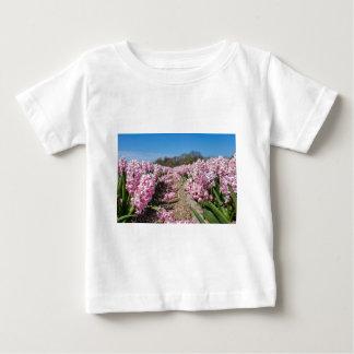 オランダのピンクのhyacinthsが付いている花分野 ベビーTシャツ