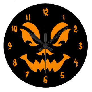オレンジおよび黒によって切り分けられるカボチャ顔 ラージ壁時計