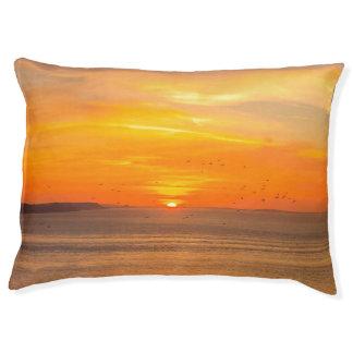 オレンジ日曜日および鳥が付いている日没の海岸 ペットベッド