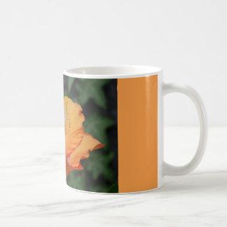 オレンジ花が付いているコーヒー・マグ コーヒーマグカップ