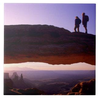 カップルはメサのアーチ頂上からの日の出を見ます タイル