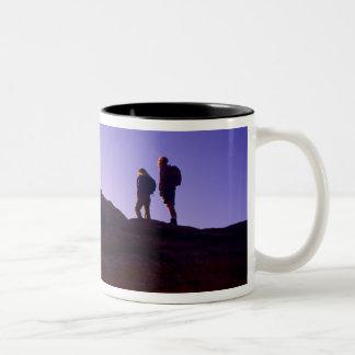 カップルはメサのアーチ頂上からの日の出を見ます ツートーンマグカップ