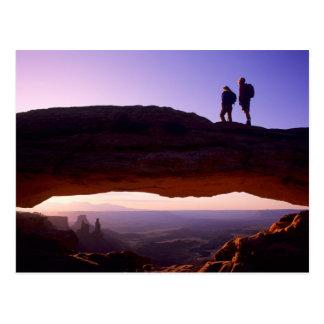 カップルはメサのアーチ頂上からの日の出を見ます ポストカード