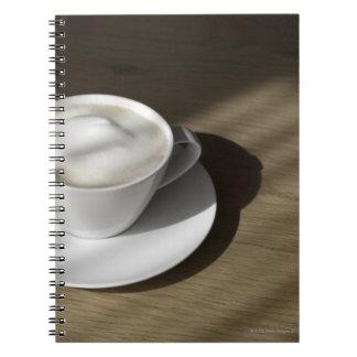 カプチーノのコーヒーのコップはカシにあります ノートブック