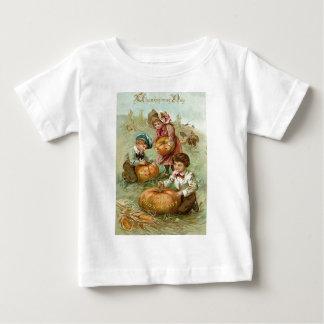 カボチャトウモロコシの三角波を切り分けている子供 ベビーTシャツ