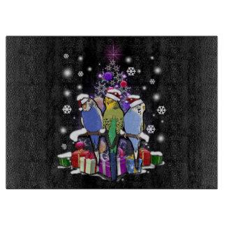 クリスマスのギフトおよび雪片とのセキセイインコ カッティングボード