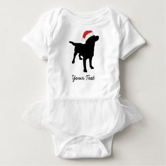 クリスマスのサンタの帽子を持つ黒い実験室犬 ベビーボディスーツ