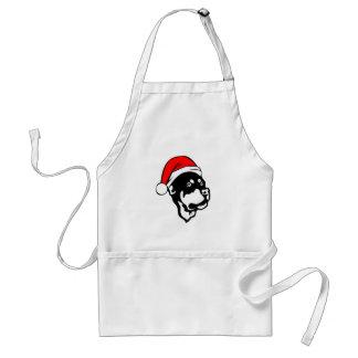 クリスマスのサンタの赤い帽子を身に着けているロットワイラー犬 スタンダードエプロン