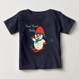 クリスマスの東海岸のベビーのかわいい雪だるまのスキー ベビーTシャツ