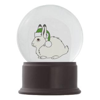 クリスマスの緑のサンタの帽子が付いている白い北極ノウサギ スノーグローブ