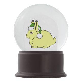 クリスマスの緑のサンタの帽子が付いている黄色い北極ノウサギ スノーグローブ