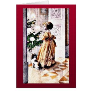 クリスマスのtreのinfrontを祈っている犬を持つ女の子 カード
