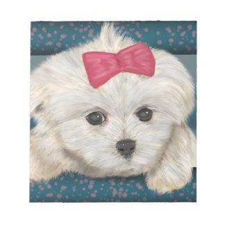 クリーム毛皮および赤いリボンを持つかわいいマルタ犬 ノートパッド