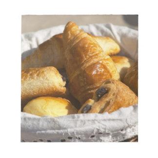 クロワッサンが付いている柳細工の朝食のバスケット、 ノートパッド