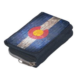 コロラド州の旗のグランジなレンガ壁のデニムの札入れ