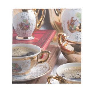 コーヒーが付いている旧式な磁器のコーヒーカップ ノートパッド