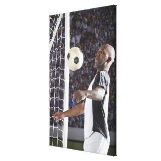 ゴールの口の中間のエアーボールに直面しているサッカーの選手 キャンバスプリント