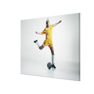 サッカーを蹴ることを準備しているメスのサッカーの選手 キャンバスプリント