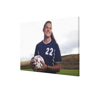 サッカーボールを握っている10代のな女の子のサッカーの選手 キャンバスプリント