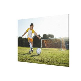 サッカー競技場のサッカーを遊んでいる若い女の子 キャンバスプリント