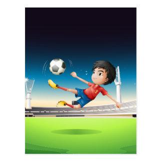 サッカー競技場の赤いユニフォームの男の子 ポストカード