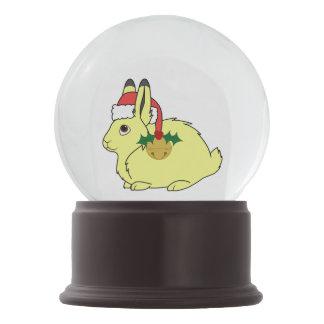 サンタの帽子及び金ゴールド鐘の黄色い北極ノウサギ スノーグローブ