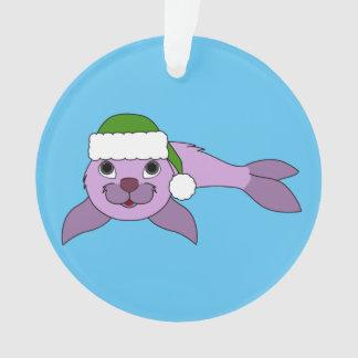 サンタの緑の帽子が付いている薄紫の子どものアシカ オーナメント