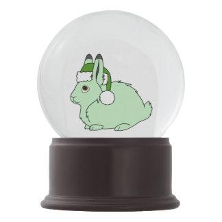 サンタの緑の帽子が付いている薄緑の北極ノウサギ スノーグローブ