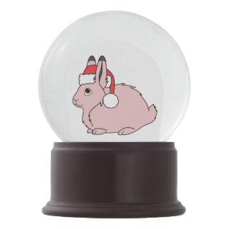サンタの赤い帽子が付いている淡いピンクの北極ノウサギ スノーグローブ
